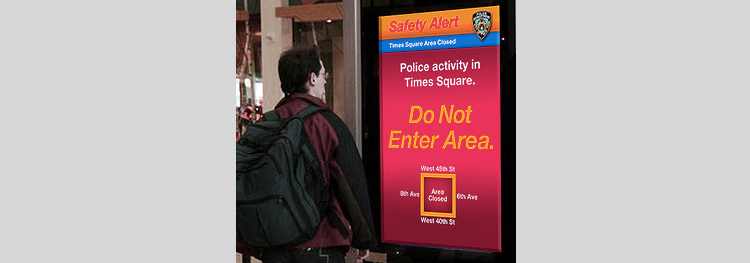 Picture of man looking at large screen reporting incident in times square.
